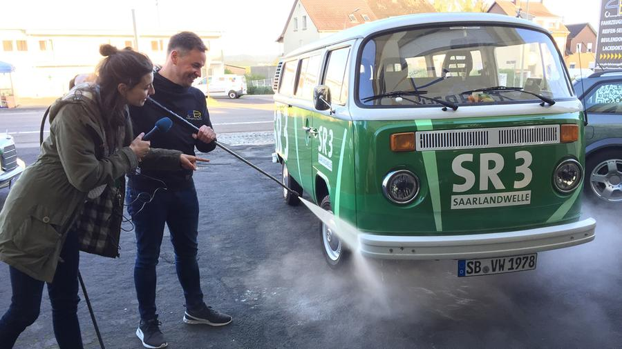Karsten Becker von PB Fahrzeugpflege und Isabell Sonnabend vom SR3 Team am GuMo Mobil